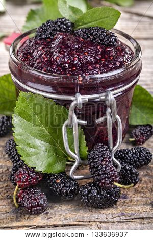 Domestic fresh mulberry jam on a rustic wooden board