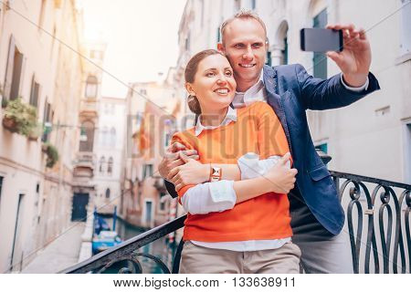 Smiling couple take a selfie photo on the old Venice street