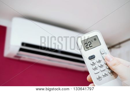 Air Conditioner Split. Hand Holding Remote Control