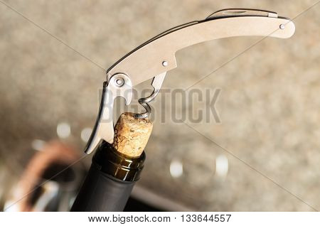 Waiter steel corkscrew opens a bottle of wine
