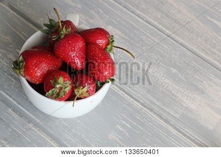 Strawberries in white cup on wooden grey desk. Stock photo.