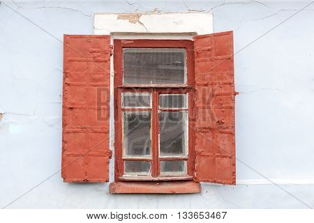 Old wooden window with metal shutters and blue background