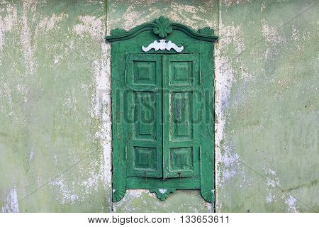 Old wooden window with closed wooden shutters