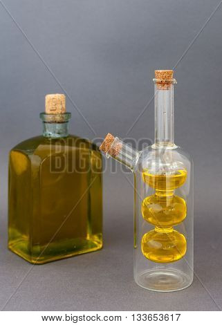 Two glass bottles with olive oil on a dark background