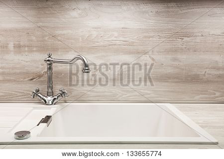 Modern designer chrome water tap over stainless steel kitchen sink.