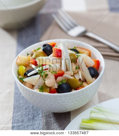 A bowl of bean salad with endive bell pepper onion olives and parsley