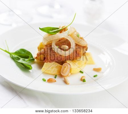 An appetizer of battered ham with fried onions pine seeds and potatoes