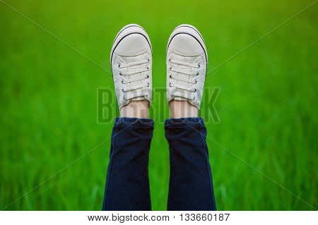 Raised up feet shod in sneakers on a green background.