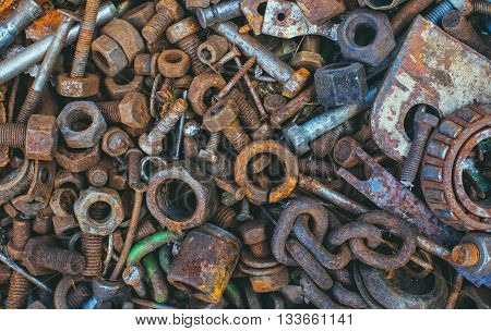Old rusty worn metal details- bolts nuts bearings chain lie in a heap.