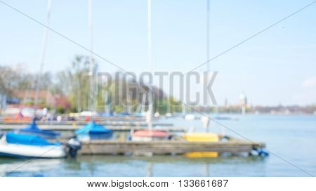 Overexposed blurred un-focused lake scene with yellow sailboat anchored at wooden jetty. Trees without leaves and blurry cityscape in the background.