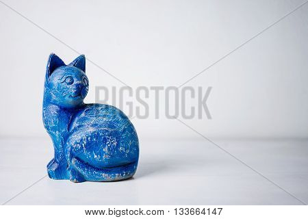 Blue wood cat on white wooden background.