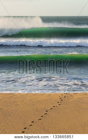 Surfer footprints on sandy beach with green waves crashing behind
