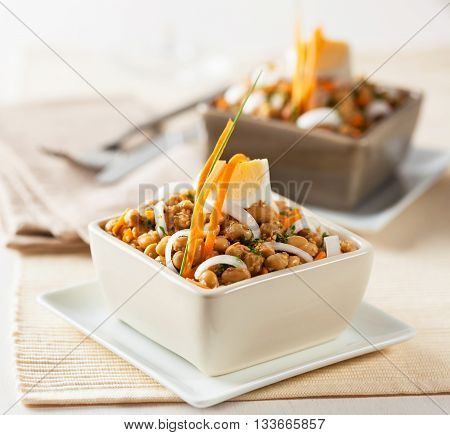 A salad with soy beans fermented wheat onion carrot and egg