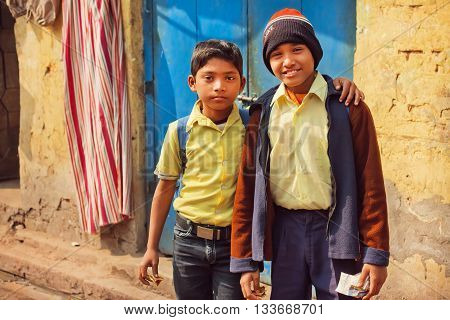 KOLKATA, INDIA - JAN 10, 2016: Unidentified schoolkids hugging on poor houses street of indian city on January 10, 2016. Kolkata's literacy rate of 87.14 perc. exceeds the all-India average of 74 perc.