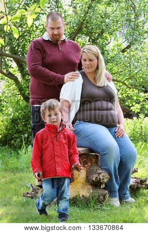 Obese farmer's family together on garden. Pregnant mother and overweight father. People working and enjoying life on countryside. Pregnancy and parenting.