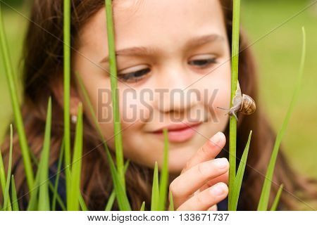 The girl with admiration watching a little snail.