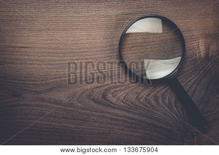 magnifying glass on the brown wooden background