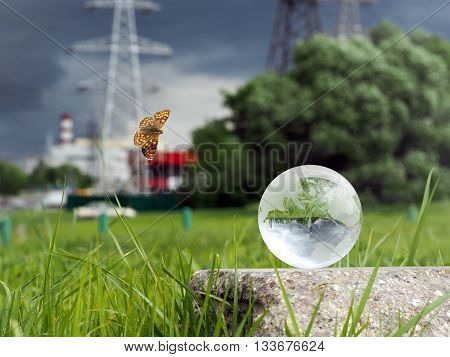 Glass ball on concrete, green grass. Flies beautiful butterfly. Background - power lines, stormy sky, cars. The concept - a source of energy, electrification, environment in big cities