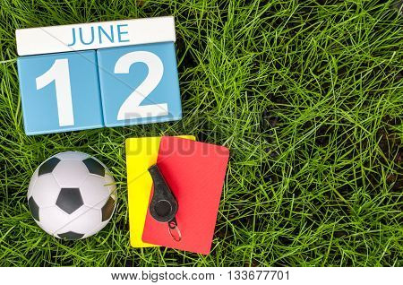 June 12th. Image of june 12 wooden color calendar on green grass background with football outfit. Summer day.