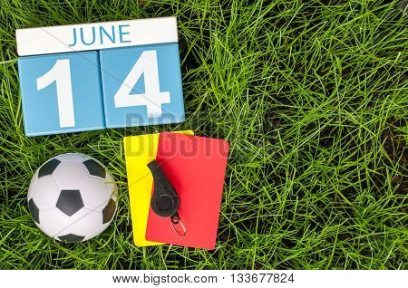 June 14th. Image of june 14 wooden color calendar on green grass background with football outfit. Summer day.