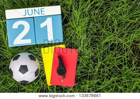 June 21st. Image of june 20 wooden color calendar on green grass background with football outfit. Summer day.
