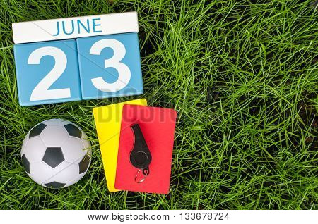 June 23rd. Image of june 23 wooden color calendar on green grass background with football outfit. Summer day.