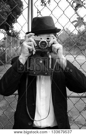 Retro style photographer with old camera. Young photographer. Photographer holding retro vintage camera. Black and white photography