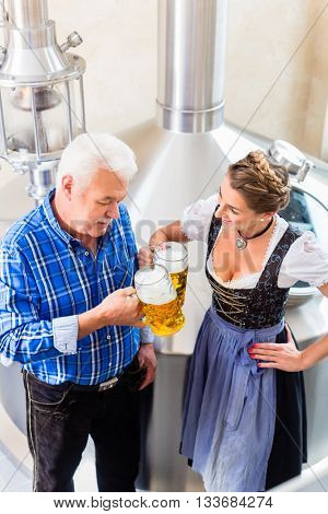 Brewer and woman toasting in beer brewery