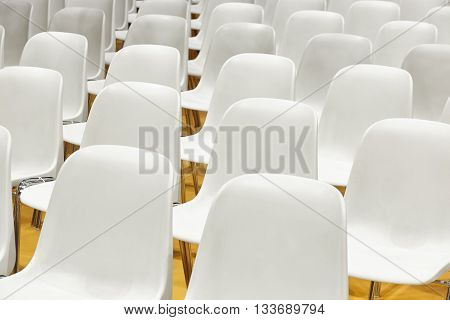Conference room with plastic chairs detail and yellow floor. Horizontal
