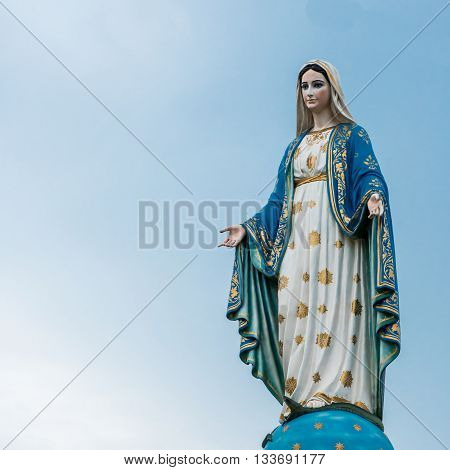 The virgin mary statue with blue sky in background