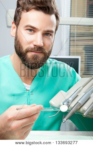 Male Doctor With Beard In Green Costume In Dental Clinic