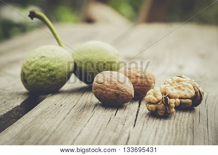 fresh walnuts on the brown wooden table background. green, unshelled and shelled nuts