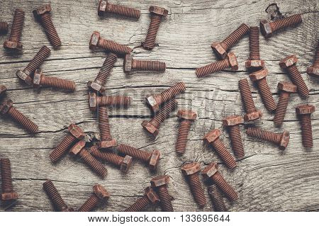 old rusty screw bolts on the wooden table background