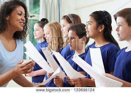 Group Of School Children With Teacher Singing In Choir