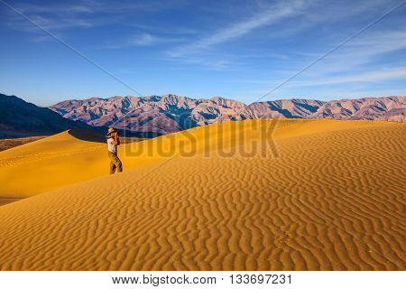 Woman in striped shirt and straw hat  photographing sand waves. Mesquite Flat Sand Dunes. Bright sunny morning in a picturesque part of Death Valley