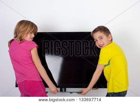 Cute kids carrying a large screen TV