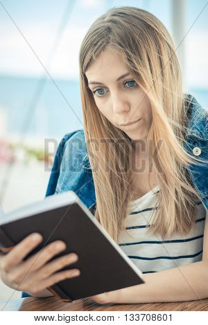 Beautiful Serious Girl In Jeans Jacket Reads Book