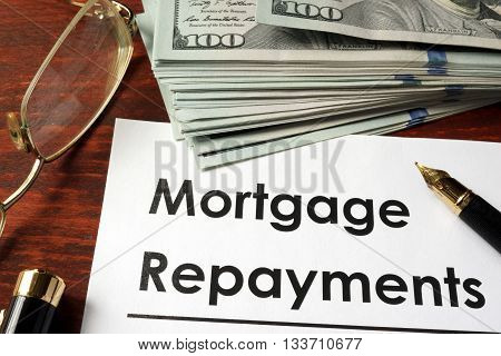 Paper with words mortgage repayments on a wooden background.