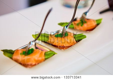 Appetizer plate of sauteed asparagus wrapped in thin slices of smoked salmon and different vegetable juice . Closeup with selective focus and shallow depth of field. poster