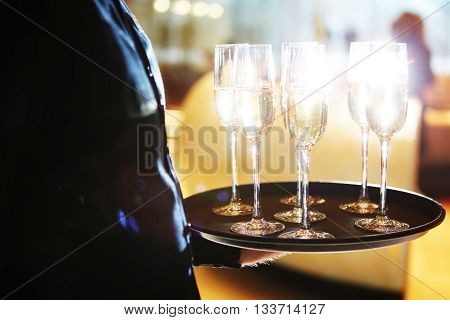 Waiter serving champagne glasses on a tray poster