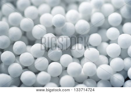 Many white small spherical homeopathic pills closeup