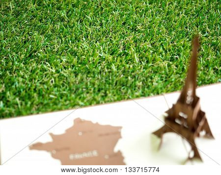 Artificial grass with blurry foreground of Eiffel tower paper model apply for European football tournament in France with copy space (selective focus)
