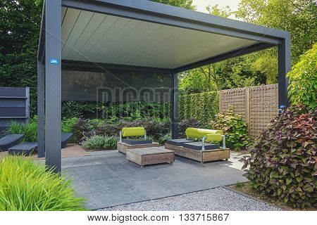 Appeltern The Netherlands July 22 2015: The Gardens of Appeltern is the inspiration garden park in the Netherlands. In this picture trendy sunloungers and overhang with trendy garden furniture.