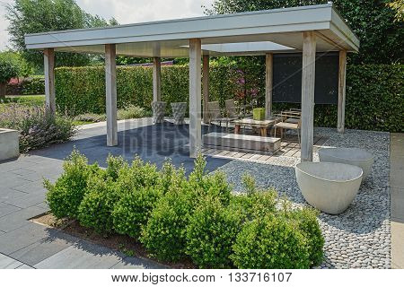 Appeltern The Netherlands July 22 2015: The Gardens of Appeltern is the inspiration garden park in the Netherlands. In this picture an open patio with garden furniture and other decorations.
