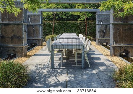 Appeltern, The Netherlands - July 22, 2015: The Gardens of Appeltern is the inspiration garden park in the Netherlands. In this picture trendy a terrace with trendy garden furniture between concrete fences.