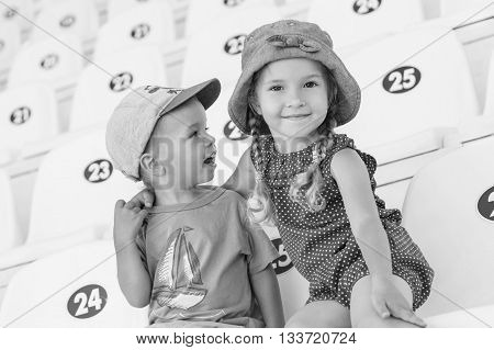 funny little children brother and sister sitting in the auditorium ( black and white )