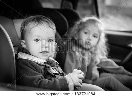 cute small children in car seats in the car ( black and white )