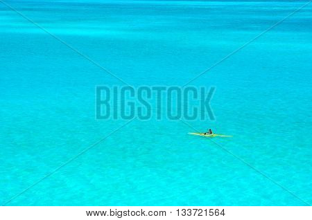 Bora Bora French Polynesia - May 6 2012: Man paddling in a yellow outrigger canoe in the clear water of the turquoise blue lagoon of Bora Bora island in the Tahiti archipelago French Polynesia.