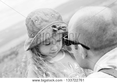 Dad kissing and soothes daughter outdoors ( black and white )