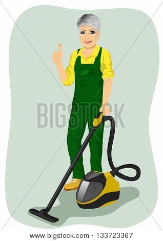 Elderly woman in green coveralls posing with a vacuum cleaner and giving thumbs up